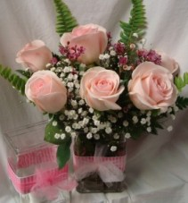 6 Pink Roses arranged in a vase with Baby's Breath with ribbon detail.