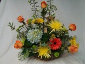 Basket of mixed flowers in oranges, yellows and  blue colors arranged.